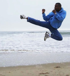 Flying side kick on the beach